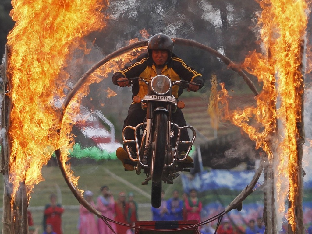 A Kashmiri policeman performs a stunt on a motorbike through a ring of fire during India's Independence Day celebrations in Srinagar. REUTERS/Danish Ismail