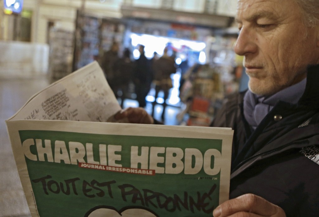 Jean Paul Bierlein reads the new Charlie Hebdo newspaper at a newsstand in Nice, France, Wednesday. AP Photo/Lionel Cironneau