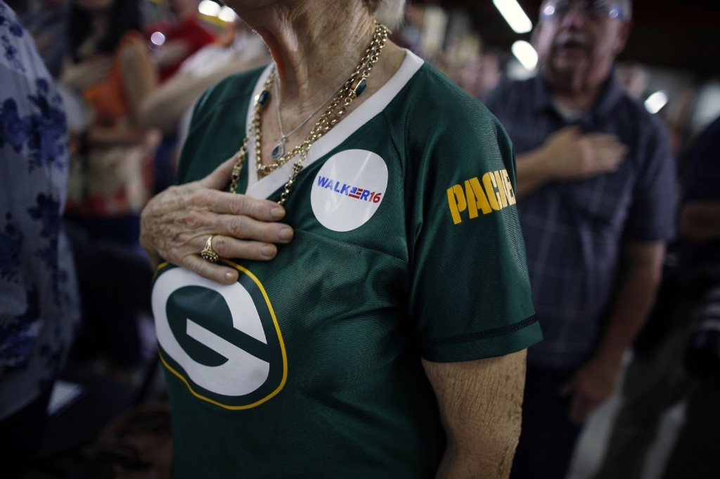 A supporter of Republican presidential candidate Scott Walker, wearing a Green Bay Packers jersey, recites the Pledge of Allegiance prior to a speech by Walker at a town hall meeting in Las Vegas. AP Photo/Isaac Brekken