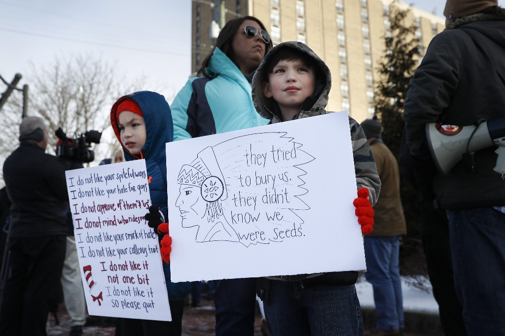 Protestors gather outside the Catholic Diocese of Covington Tuesday, Jan. 22, 2019, in Covington, Ky. The diocese in Kentucky has apologized after videos emerged showing students from a Catholic boys' high school mocking Native Americans outside the Lincoln Memorial on Friday after a rally in Washington. (AP Photo/John Minchillo)
