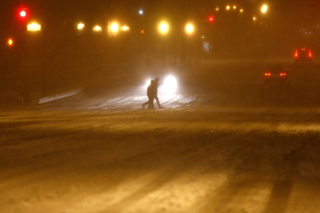 People cross an empty street after a winter storm arrived in Washington. REUTERS/Carlos Barria
