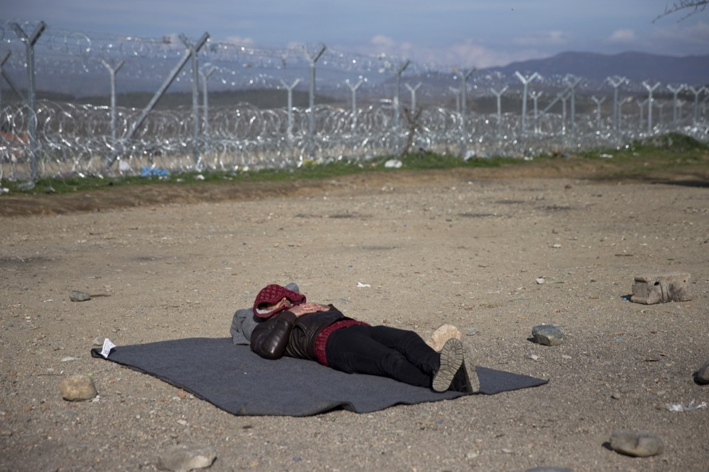 A stranded Syrian migrant sleeps in front of the wire fence that separates the Greek side from Macedonia, at the northern Greek border station of Idomeni. AP Photo/Petros Giannakouris