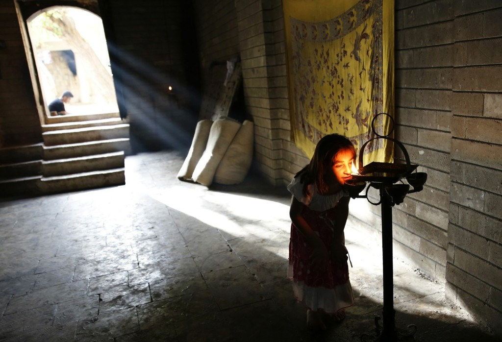 A displaced girl from the minority Yazidi sect, who fled violence in the Iraqi town of Sinjar, worships at their main holy temple Lalish in Shikhan. REUTERS/Ahmed Jadallah
