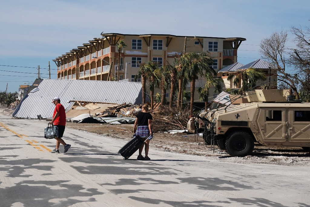 People carry suitcases after Hurricane Michael in Mexico Beach, Florida, U.S., October 12, 2018. REUTERS/Carlo Allegri