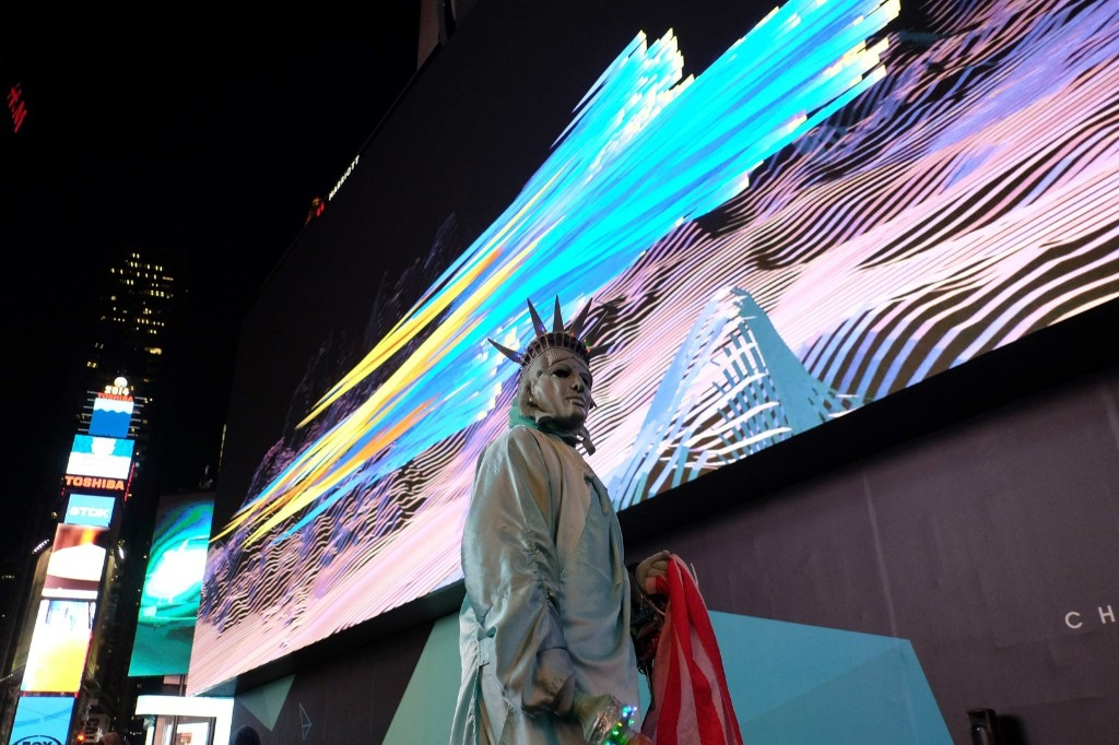 A man dressed up as the Statue of Liberty waits under an eight-story tall digital billboard in Times Square. JEWEL SAMAD/AFP/Getty Images
