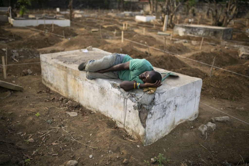 A grave digger sleeps near the graves of Ebola victims at a cemetery in Freetown. REUTERS/Baz Ratner