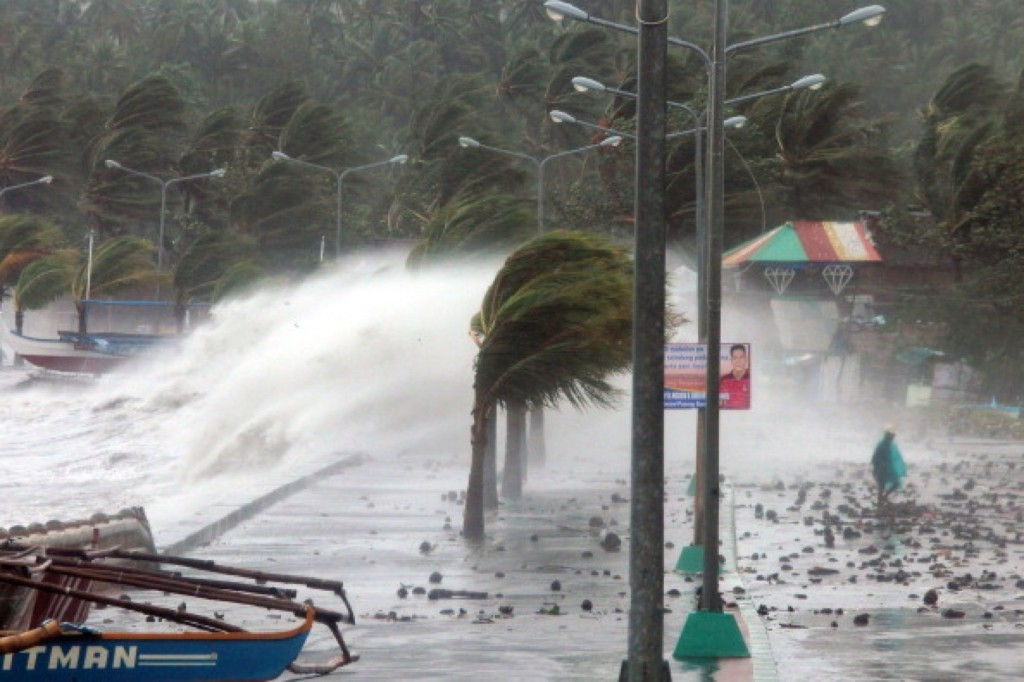 A resident, right, walks past high waves pounding the sea wall amid strong winds as Typhoon Haiyan hit the city of Legaspi, Albay province, south of Manila on Friday. One of the most intense typhoons on record terrified millions as monster winds tore roofs off buildings and giant waves washed away flimsy homes. Charism SAYAT/AFP/Getty Images