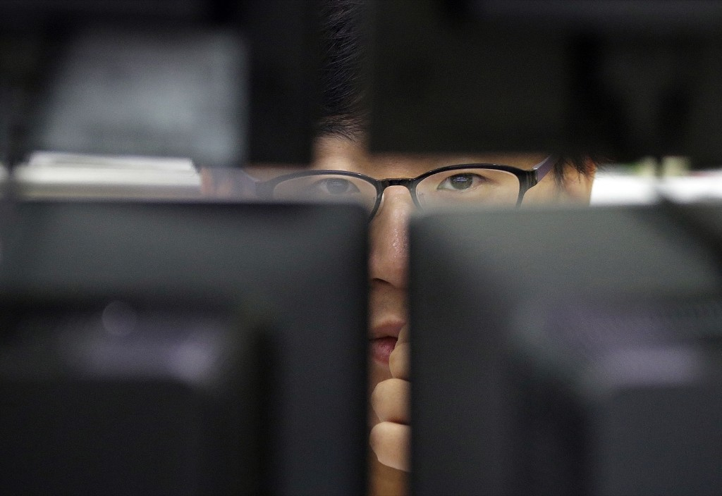 A currency trader watches monitors at the foreign exchange dealing room of the KEB Hana Bank headquarters in Seoul. AP Photo/Ahn Young-joon