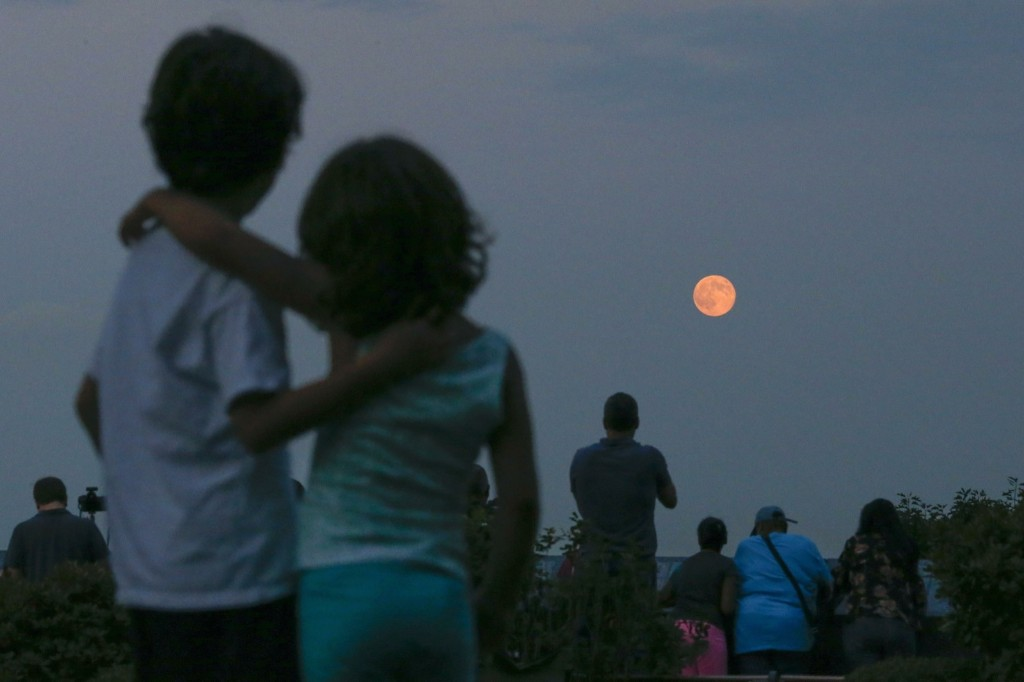 Children watch supermoon rising over the skyline of New York from the Eagle Rock Reservation in West Orange, New Jersey. REUTERS/Eduardo Munoz