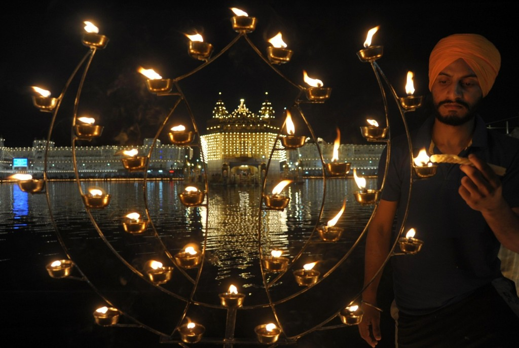 An Indian Sikh devotee lights candles during Diwali at the illuminated Golden Temple in Amritsar. NARINDER NANU/AFP/Getty Images