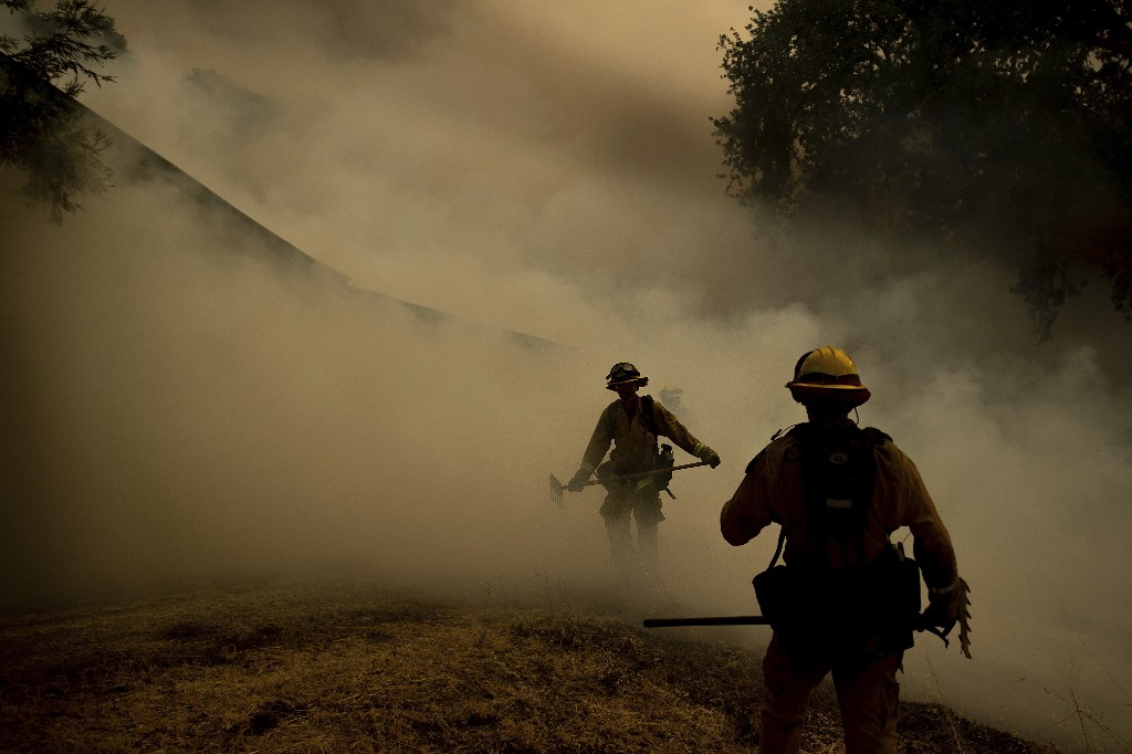 A firefighter walks through smoke while fighting to save Olof Cellars winery in Lakeport, Calif., Monday, July 30, 2018. A pair of wildfires that prompted evacuation orders for nearly 20,000 people barreled Monday toward small lake towns in Northern California, and authorities faced questions about how quickly they warned residents about the wildfires. (AP Photo/Noah Berger)