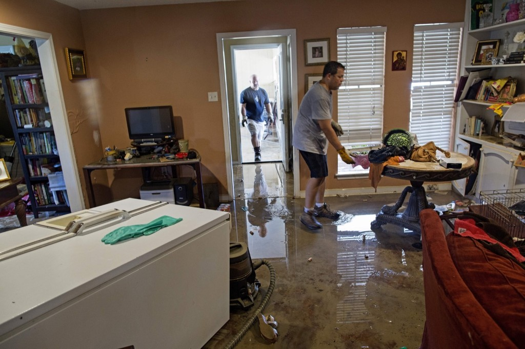 Raymond Lieteau pulls furniture out of his flood-damaged home with the help of his friend Danny Lemoine in Baton Rouge. AP Photo/Max Becherer