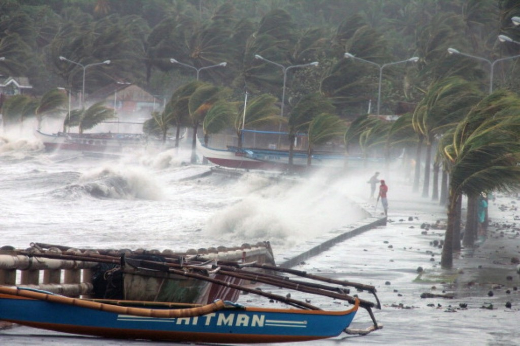 Residents stand along a sea wall in Legaspi, Albay province, south of Manila. One of the most intense typhoons on record has so far killed three people. Charism SAYAT/AFP/Getty Images