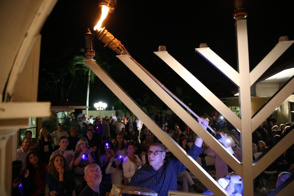 Arthur Sotloff, father of slain journalist Steven Sotloff, uses a torch to light the first candle of Hanukkah on the menorah at the Chabad Center of Kendall in Pinecrest, Fla. Joe Raedle/Getty Images