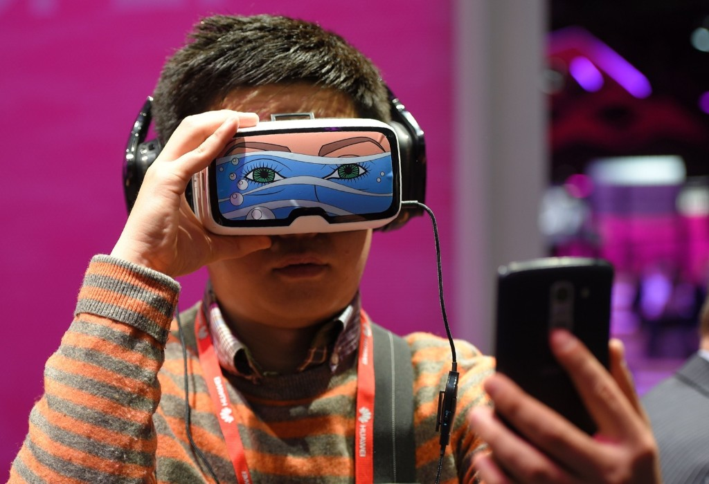 A boy takes a selfie photo as he tests the 'Oculus VR' virtual reality device during the Mobile World Congress in Barcelona. LLUIS GENE/AFP/Getty Images