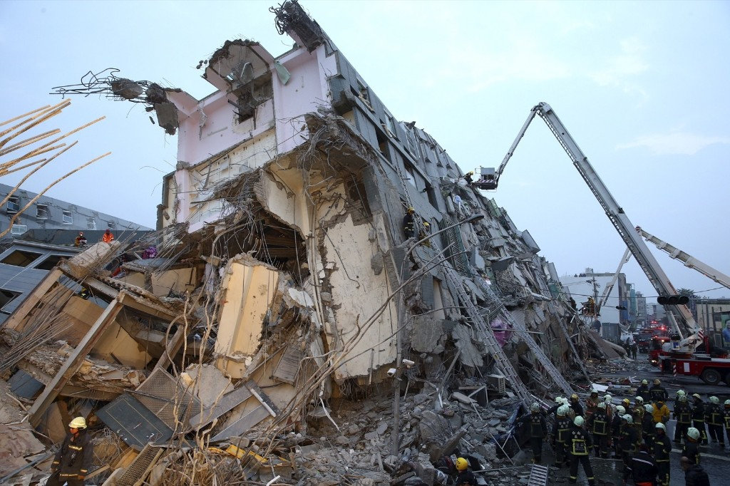 Rescue personnel work at a damaged building after an earthquake in Tainan. REUTERS/Stringer