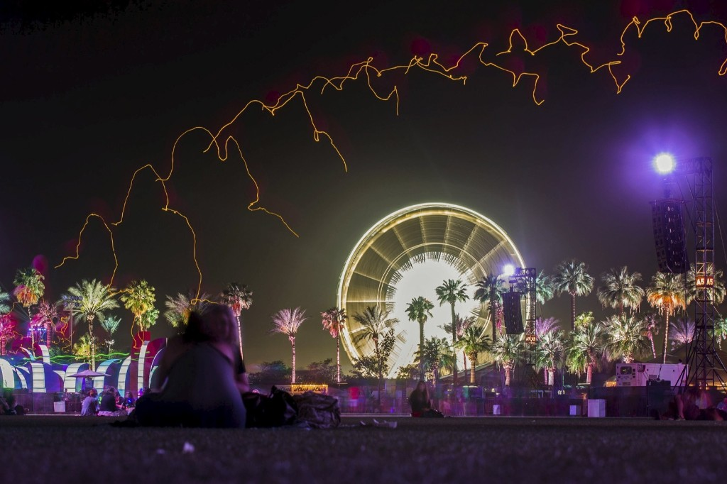 People sit under a row of lit balloons in front of the ferris wheel. REUTERS/Lucy Nicholson