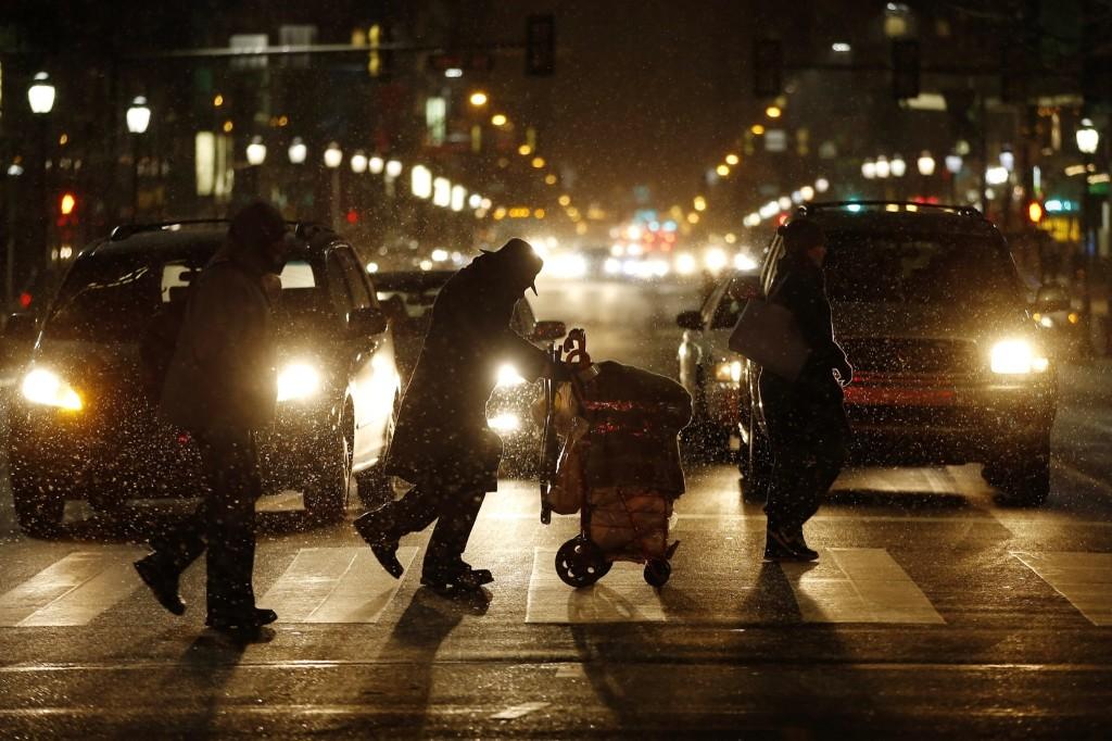 People walk across Market Street in Philadelphia as snow falls during the evening commute on Friday. AP Photo/Matt Slocum