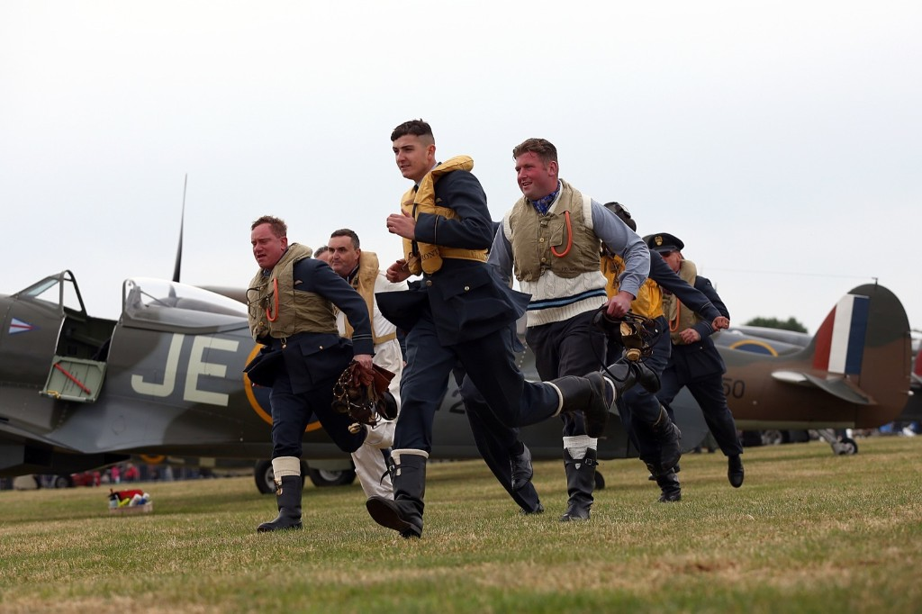 Historical reenactors take part in a 'scramble' as they rush to their aircraft in the event of an attack, Tuesday, in Biggin Hill, England. Carl Court/Getty Images