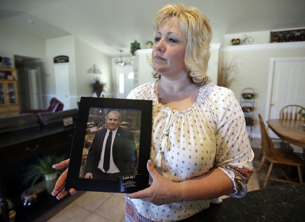 FILE - In this July 13, 2016 file photo, Laurie Holt holds a photograph of her son Joshua Holt at her home in Riverton, Utah. Holt, a Utah woman who spent nearly two years pushing to get her son freed from a Venezuelan jail, has died at age 50. Former U.S. Rep. Mia Love said Monday, Feb. 11, 2019, that Holt died unexpectedly Sunday at her home in the Salt Lake City suburb of Riverton. Love says Laurie Holt's husband Jason Holt went to wake her for church and found her unresponsive. (AP Photo/Rick Bowmer, File)