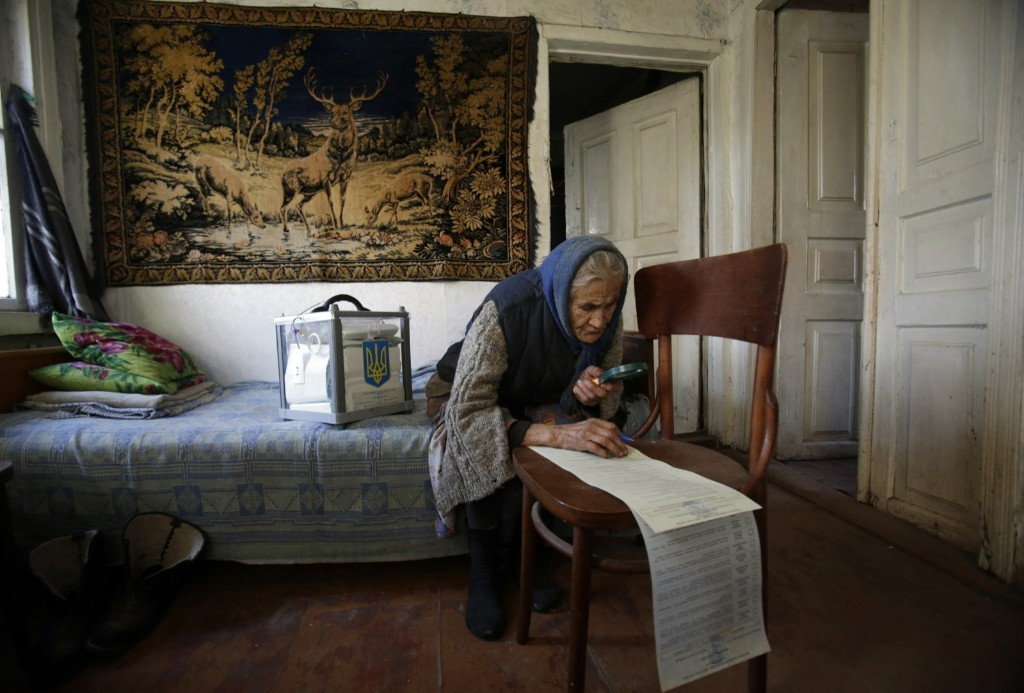 A woman uses a magnifying glass to read her ballot while voting at home in the village of Gornostaypol, near Kiev. AFP PHOTO/ANATOLII STEPANOV