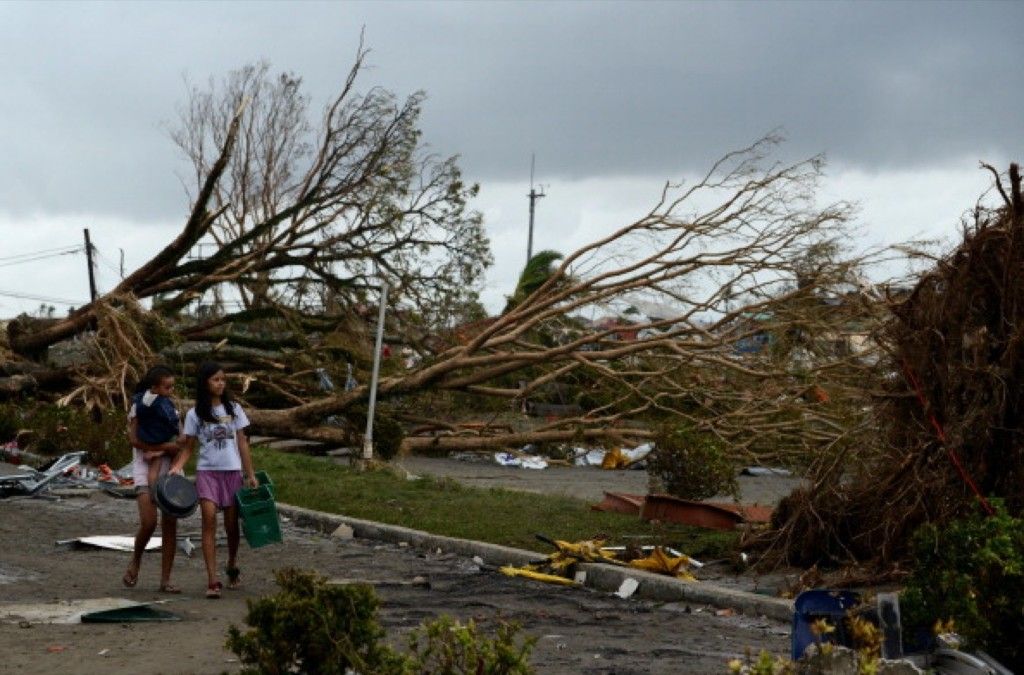 Women walk past fallen trees and destroyed houses in the aftermath of Super Typhoon Haiyan in Tacloban. NOEL CELIS/AFP/Getty Images