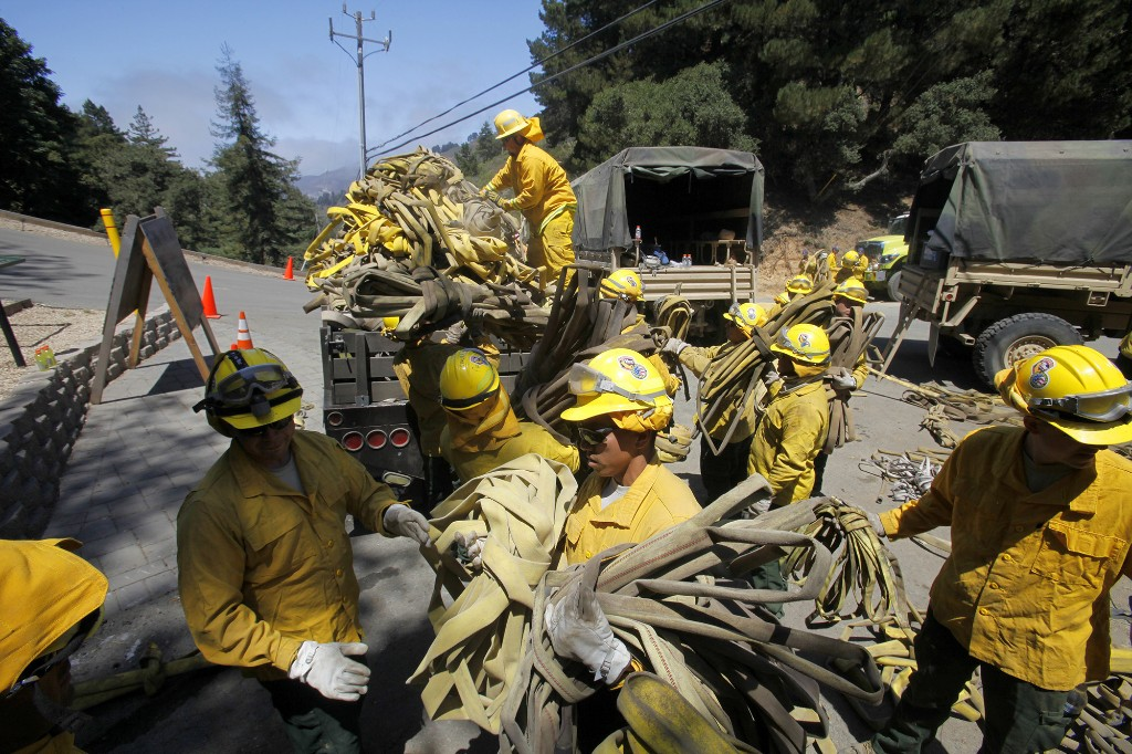 """FILE - In this Aug. 6, 2016 file photo, members of the California National Guard help load about 5 miles of used wildland fire hose in Palo Colorado Canyon, south of Monterey Calif., during efforts to fight the Soberanes Fire. When a fire burned across Big Sur two years ago and threatened hundreds of homes scattered on the scenic hills, firefighters responded with overwhelming force, attacking flames from the air and ground. The so-called Soberanes Fire burned its way into the record books as the most expensive wildland firefight in U.S. history in what a new report calls """"an extreme example of excessive, unaccountable, budget-busting suppression spending that is causing a fiscal crisis in the U.S. Forest Service."""" (Vern Fisher/The Monterey County Herald via AP)"""