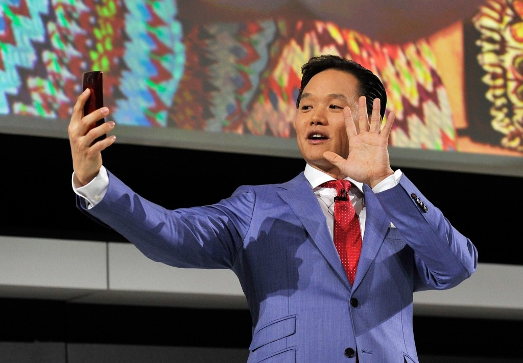 LG Electronics MobileComm's Frank Lee uses a hand gesture to activate the LG G Flex 2 smartphone for a selfie. David Becker/Getty Images
