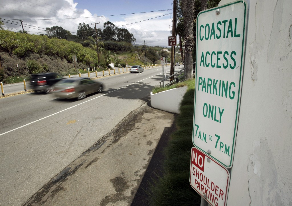 FILE - In this April 20, 2007 file photo a sign directing visitors to two parking spaces next at a coastal access gate for Escondido Beach is shown on Pacific Coast Highway in Malibu, Calif. A new smartphone app that shows users a map of more than 1,500 access points along the California coast was created with help from a tech billionaire whose elaborate wedding ran afoul of state regulators. (AP Photo/Reed Saxon, File)