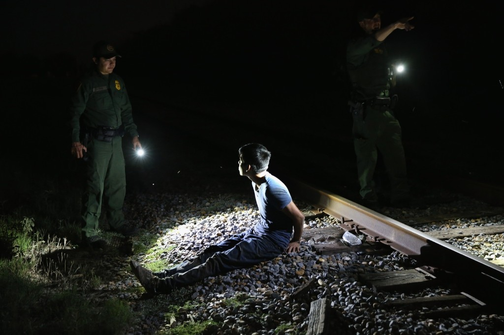 US border patrol agents detain an undocumented immigrant along a railroad track near the Rio Grande River in McAllen, Texas. John Moore/Getty Images