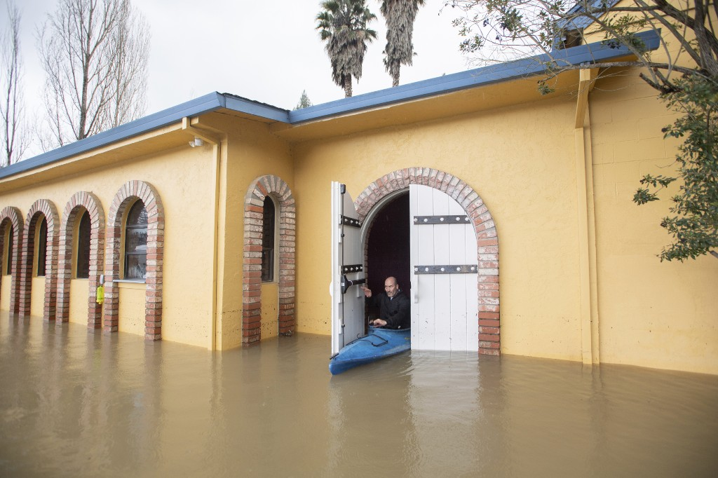 Jay Michael Tucker kayaks through the flooded Surrey Resort as the Russian River flows through it in Guerneville, Calif., Friday, Feb. 15, 2019. Streets and low-lying areas flooded as the Russian River swelled above its banks Friday. (AP Photo/Josh Edelson)