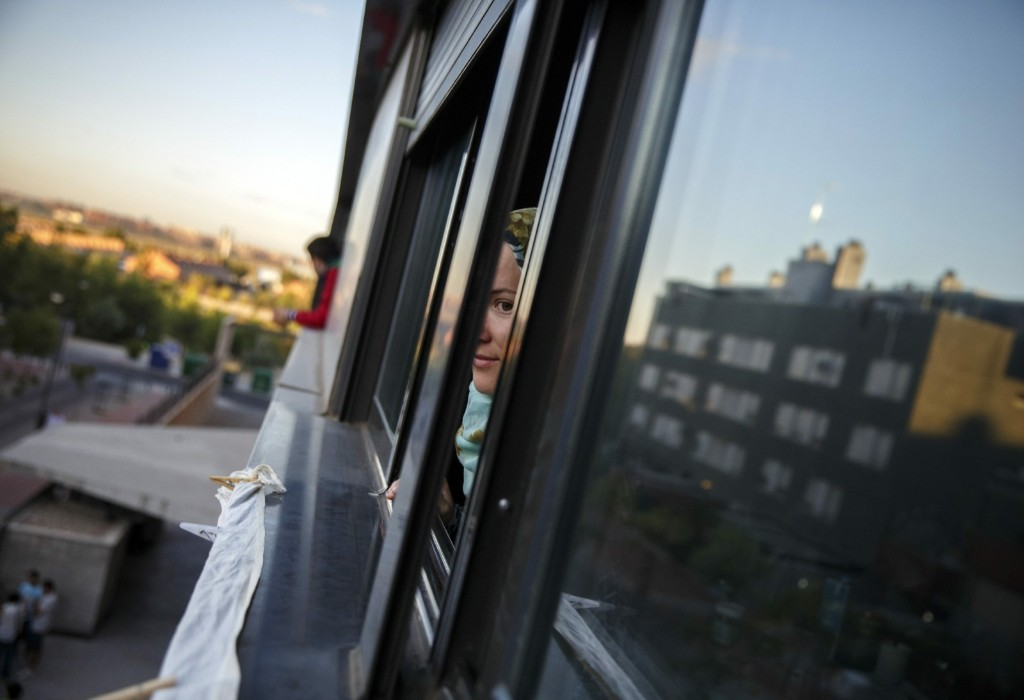 Jamila Berrabeh peers out of a window in Madrid before learning that her eviction had been temporally suspended. REUTERS/Andrea Comas