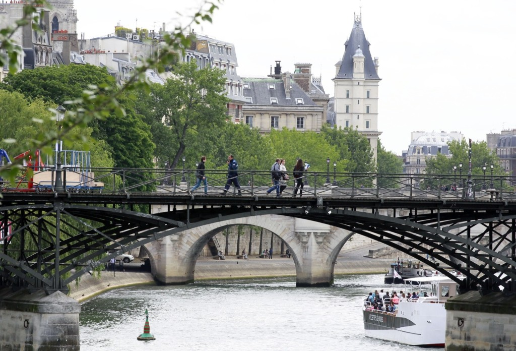 People cross the mostly lock-free famed Pont des Arts bridge in Paris, Monday June 1, 2015. AP Photo/Remy de la Mauviniere