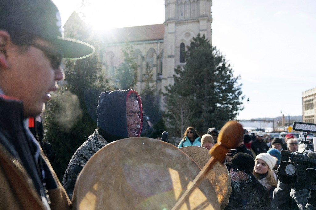 Sleepy Eye Lafromboise, center, and his son Eshtakaba, both of the Sioux Nation, sing during a gathering of Native American supporters in front of the Catholic Diocese in Covington, Ky., Tuesday, Jan. 22, 2019. (AP Photo/Bryan Woolston)