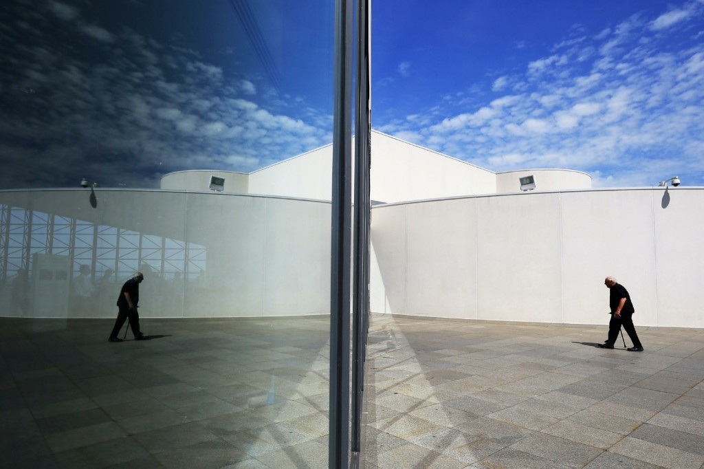 A visitor is reflected in a window at the John F. Kennedy Presidential Library in Boston. REUTERS/Brian Snyder