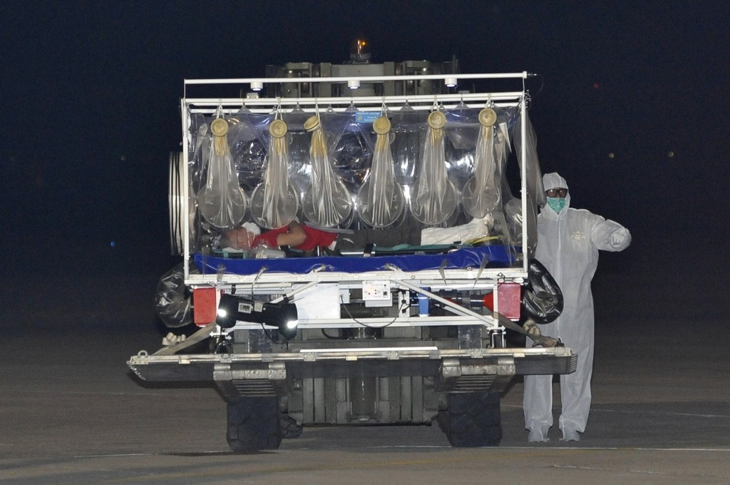 Staff of the emergency medical services transport the Italian doctor who contracted Ebola while working in Sierra Leone as he arrives at the Pratica di Mare military airport in Rome. REUTERS/Italian Airforce