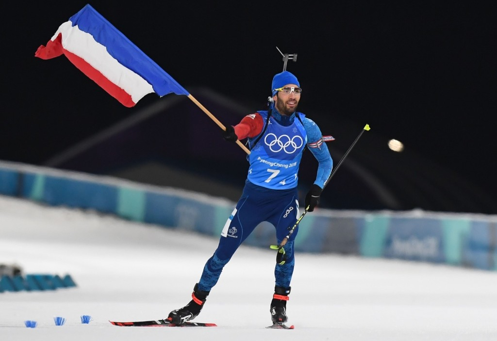 France's Martin Fourcade holds the national flag as the team wins gold in the mixed relay biathlon event. FRANCK FIFE/AFP/Getty Images