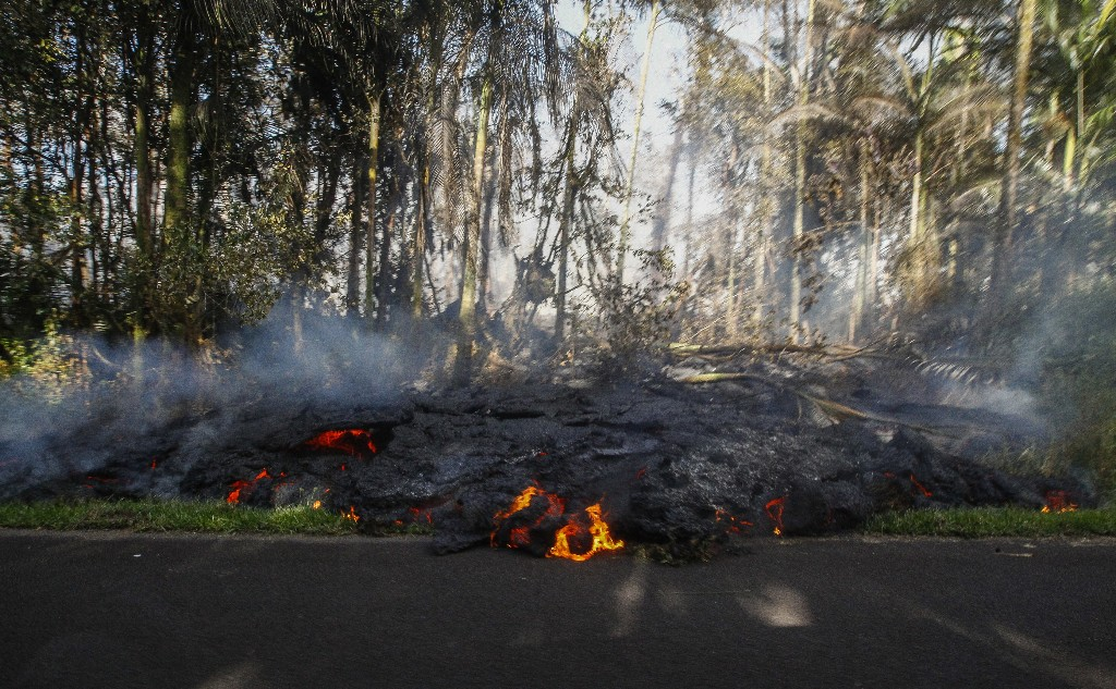 In this Sunday, May 6, 2018, photo, lava creeps onto the pavement on Luana Street in the Leilani Estates subdivision in Pahoa, Hawaii. Hawaii's Kilauea volcano has destroyed homes and spewed lava hundreds of feet into the air, leaving evacuated residents unsure how long they might be displaced. (Jamm Aquino/Honolulu Star-Advertiser via AP)