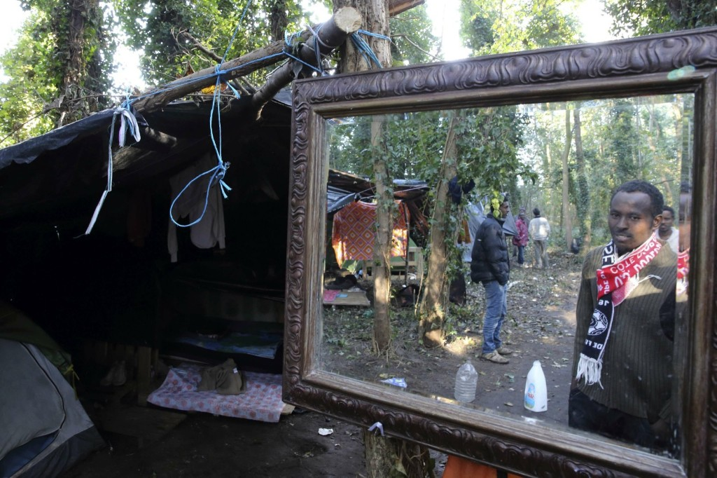 "An Ethiopian migrant is reflected in a mirror close to his makeshift shelter in the woods, known locally as the ""jungle"", near the harbour of Calais in northern France. REUTERS/Pascal Rossignol"