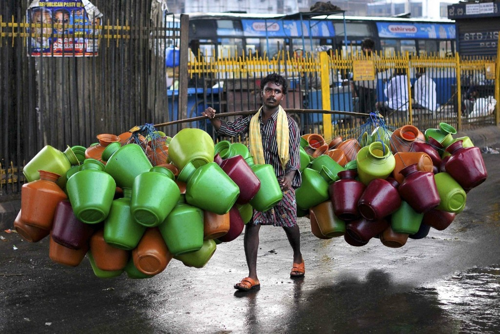 A man carries empty water pitchers for sale in a Bangalore market. REUTERS/Abhishek N. Chinnappa