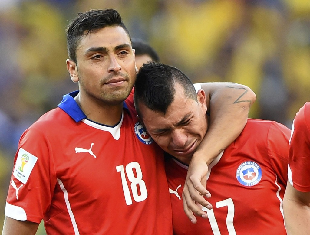 Chile's Gonzalo Jara comforts teammate Gary Medel after dramatic loss to Brazil. REUTERS/Dylan Martinez