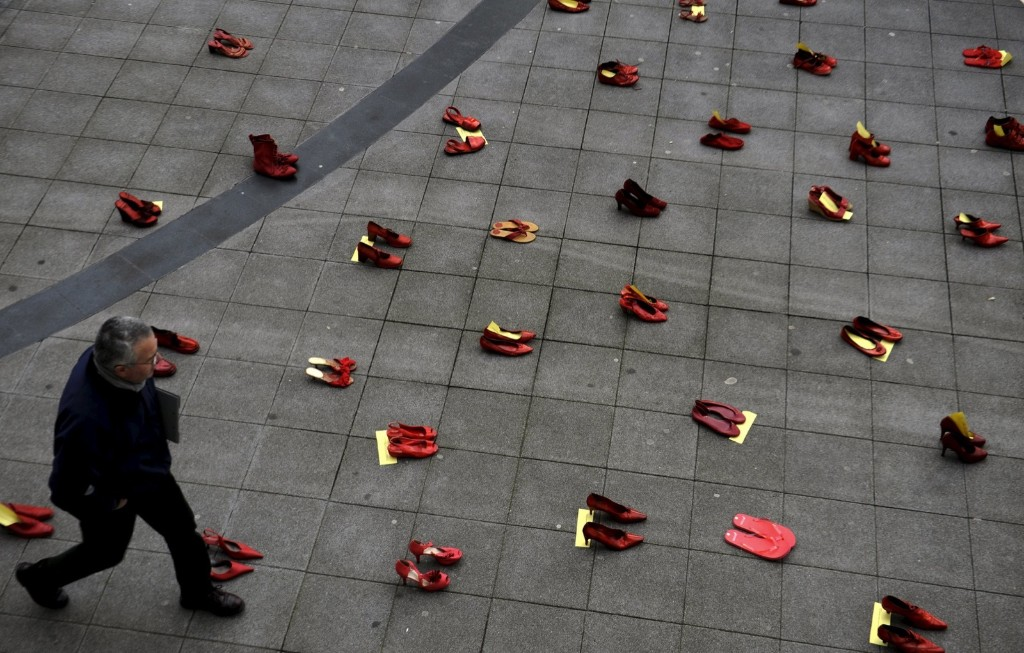 A man walks past a group of red shoes used for a performance to denounce violence against women organized by Amnesty International during International Women's Day in Gijon, Spain. REUTERS/Eloy Alonso
