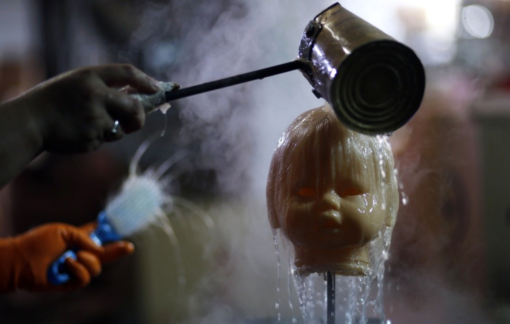 An employee pours water over a doll's head before brushing its hair inside a toy factory in Buenos Aires. REUTERS/Marcos Brindicci