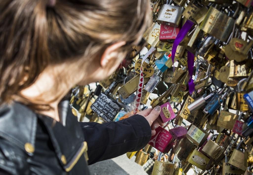 A tourist looks at a love padlocks on the Pont des Arts bridge, Monday, in Paris, France. Geoffroy Van der Hasselt/Anadolu Agency/Getty Images