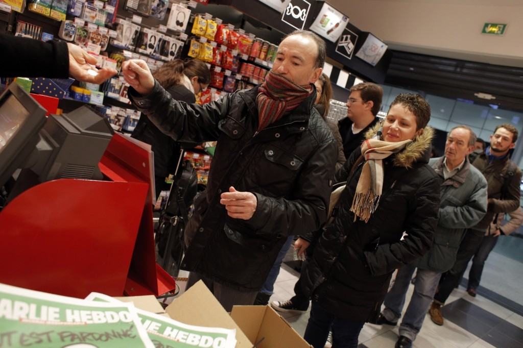 People line up to buy Charlie Hebdo newspapers at a newsstand in Paris, Wednesday. AP Photo/Christophe Ena