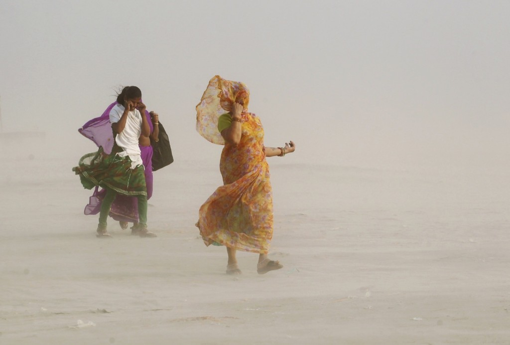 Women cover themselves as they walk on the banks of the river Ganges during a dust storm in Allahabad. REUTERS/Jitendra Prakash