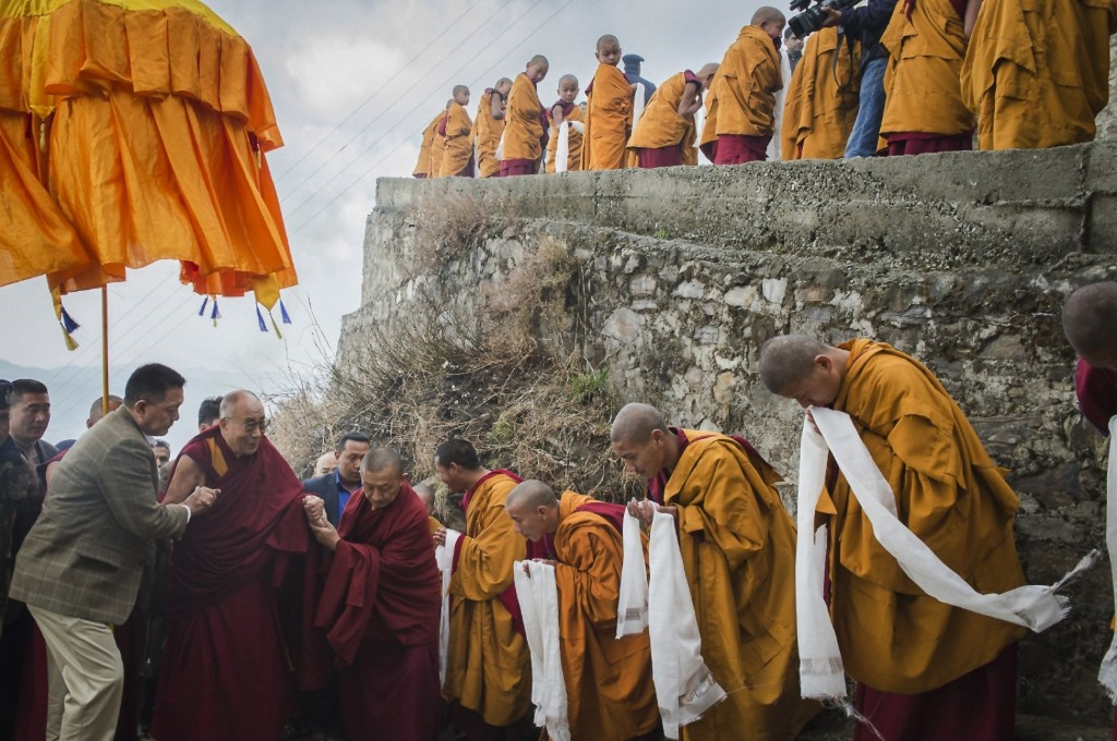 Tibetan Buddhist Monks welcome the Dalai Lama as he arrives at the Jhonang Takten Phuntsok Choeling monastery in Shimla, India. AP Photo/Tenzin Choejor