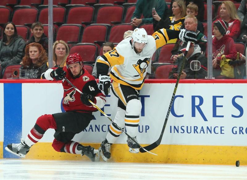 Jan 18, 2019; Glendale, AZ, USA; Pittsburgh Penguins right wing Bryan Rust (17) battles for the puck against Arizona Coyotes defenseman Niklas Hjalmarsson (4) in the first period at Gila River Arena. Mandatory Credit: Mark J. Rebilas-USA TODAY Sports