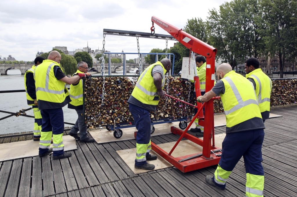 Paris city employees remove a railing loaded with locks on the famed Pont des Arts bridge in Paris, Monday. AP Photo/Remy de la Mauviniere