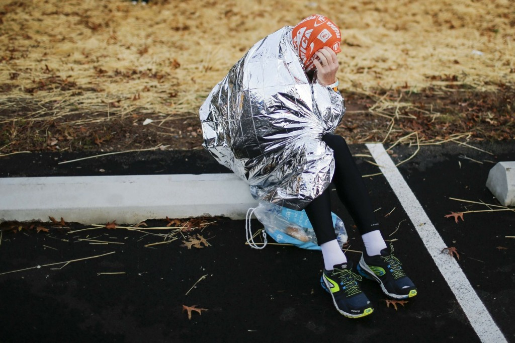 A runner covers himself from the low temperatures and strong wind before the start. REUTERS/Eduardo Munoz